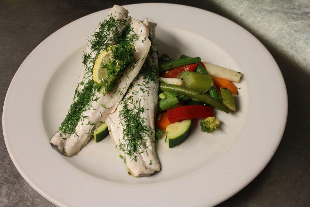 Seebarsch, gedämpft mit frischen grünen Kräutern, serviert mit Kartoffelpüree und Saisongemüse im Restaurant The Pantry in Amsterdam.